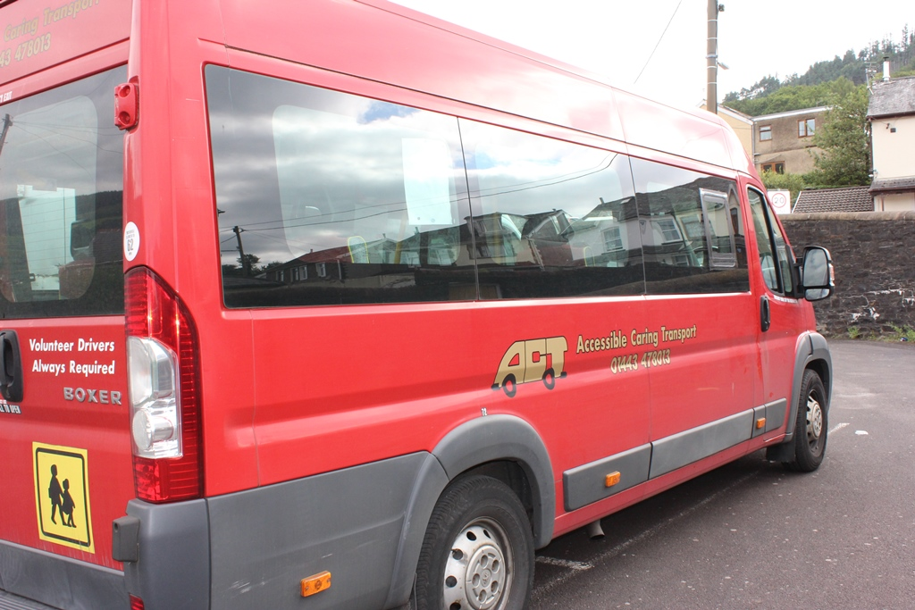 Side view of a red ACT wheelchair accessible bus