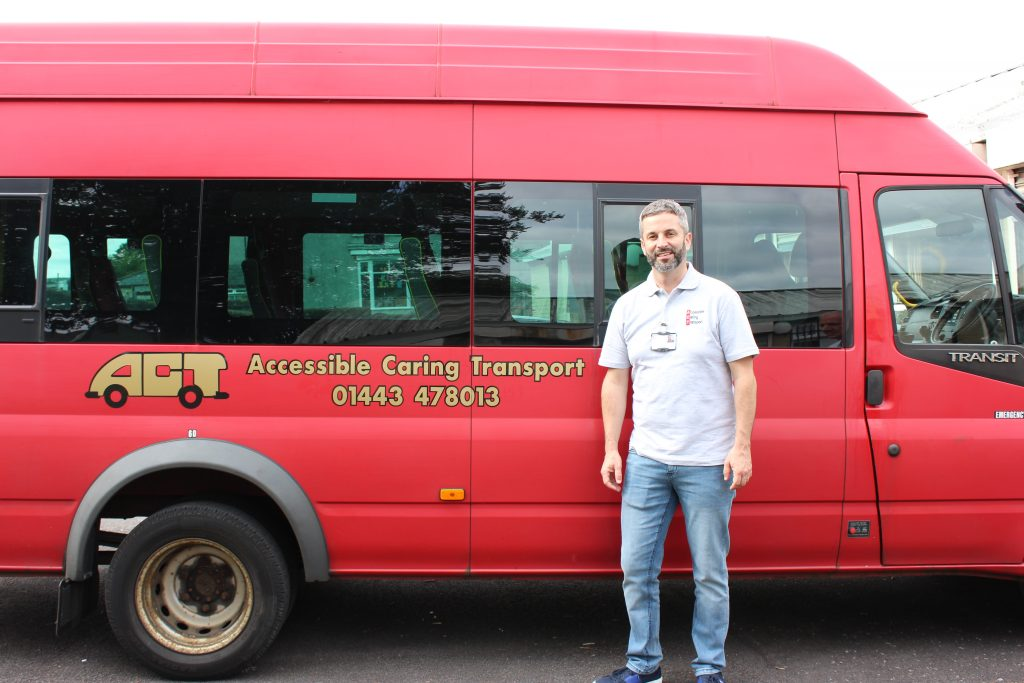 Trustee Greg Davies standing in front of an ACT bus