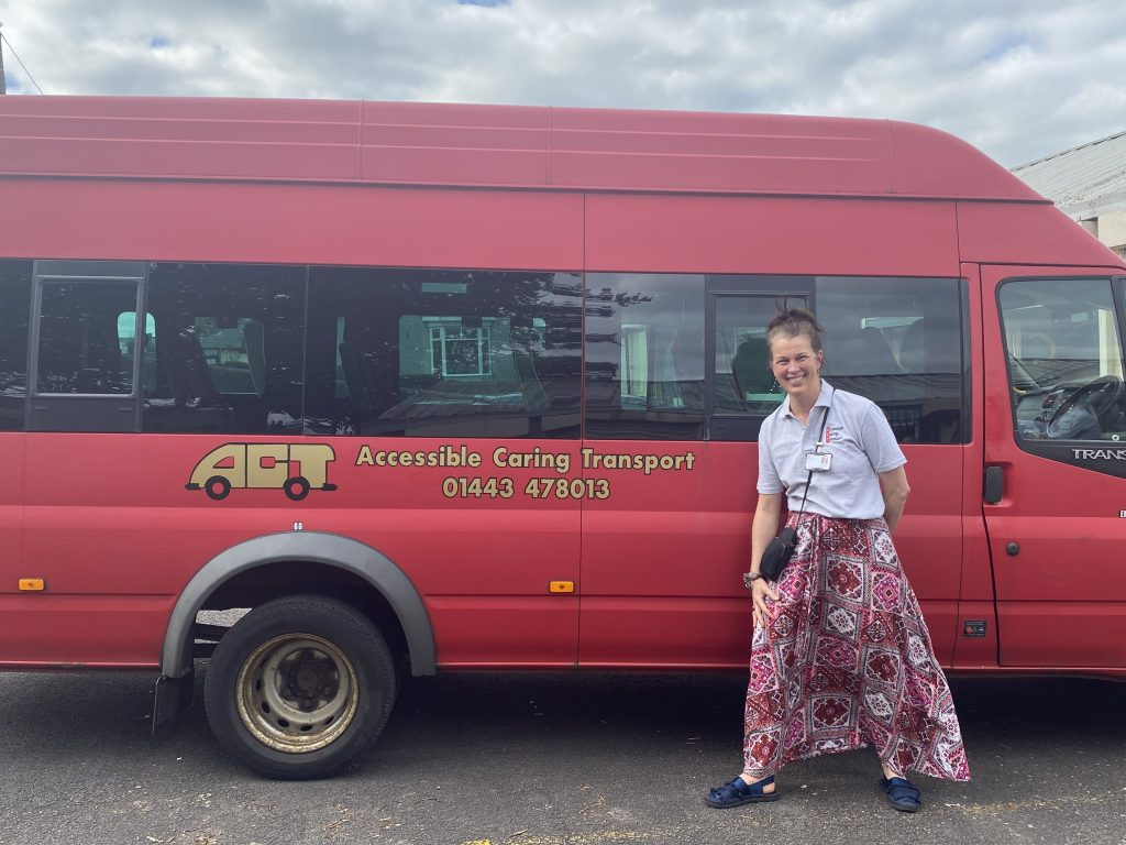 Honorary Secretary Rhian Grundy standing in front of an ACT bus