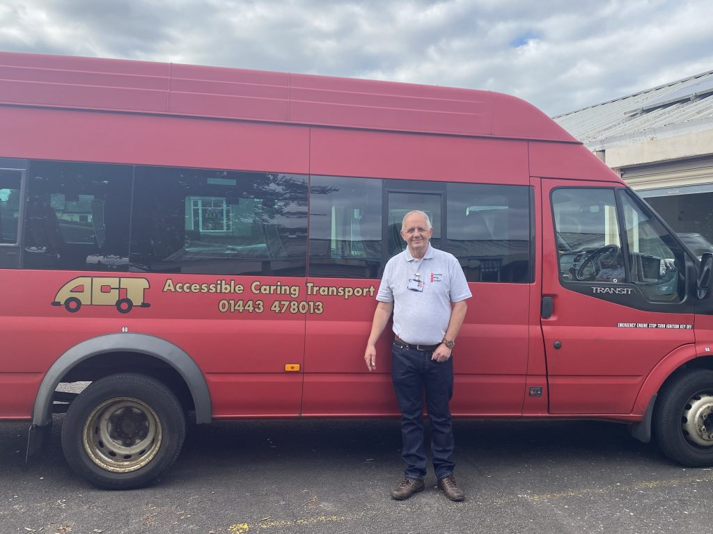 Trustee Martyn Brown standing in front of an ACT bus